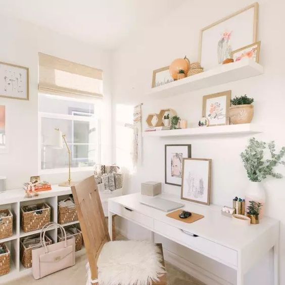 a small neutral home office with open shelves, a simple desk, a storage unit with baskets and woven shades