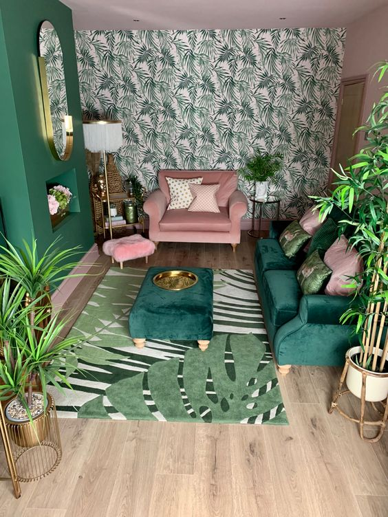 a small tropical living room with a tropical leaf wall, a green sofa and ottoman, a pink chair, touches of gold