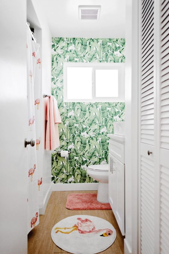 a small tropicla bathroom with a tropical leaf wallpaper wall, white appliances and a flamingo print shower curtain