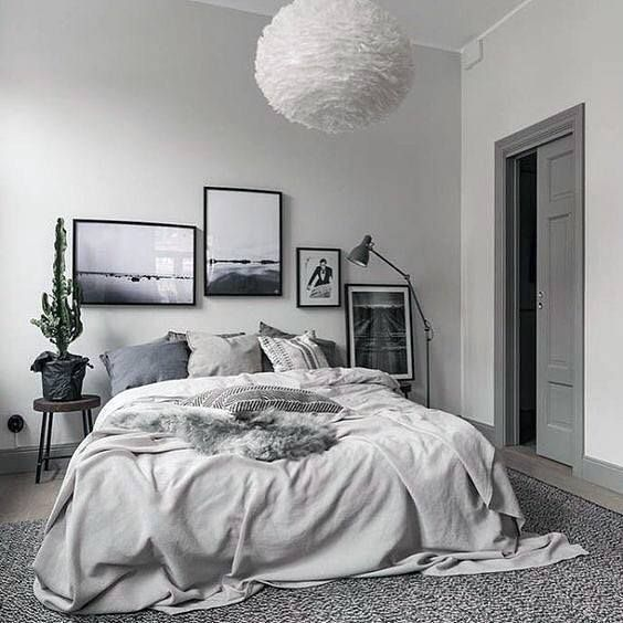 a soothing grey bedroom with a dramatic gallery wall, grey and blue bedding, a fluffy pendant lamp