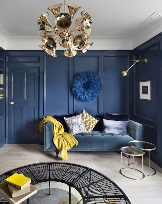 a sophisticated living room with navy paneled walls, a blue sofa, a gold chandelier and lamps and mustard accents