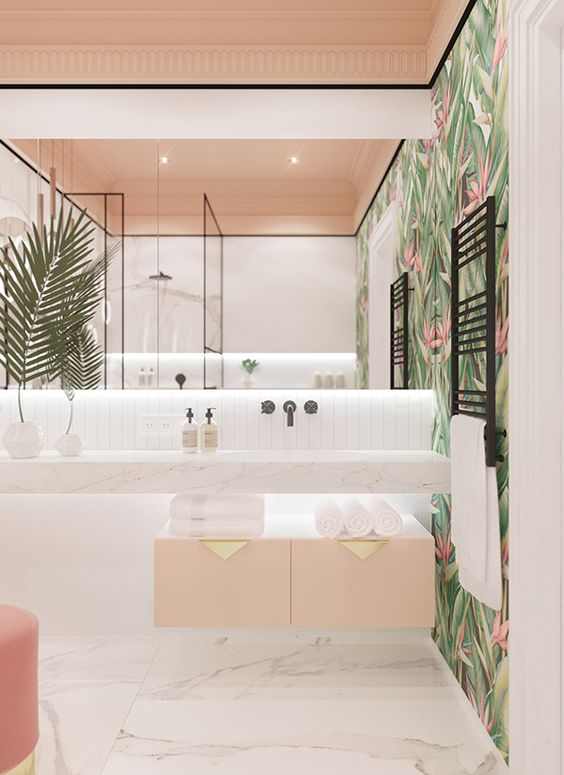 a spacious tropical bathroom with tropical wallpaper, a blush cabinet with gold handles, a pink ottoman and a large mirror