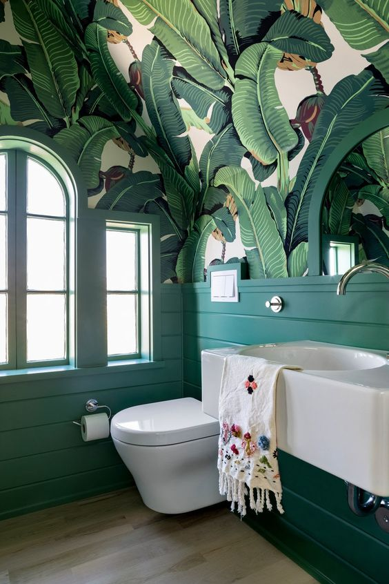 a statement tropical bathroom with banana leaf wallpaper on the ceiling, emerald panels and white appliances for a bold look