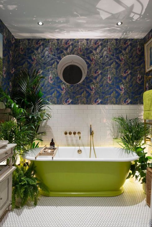 a statement tropical bathroom with moody wallpaper, a neon green tub and towels and potted greenery