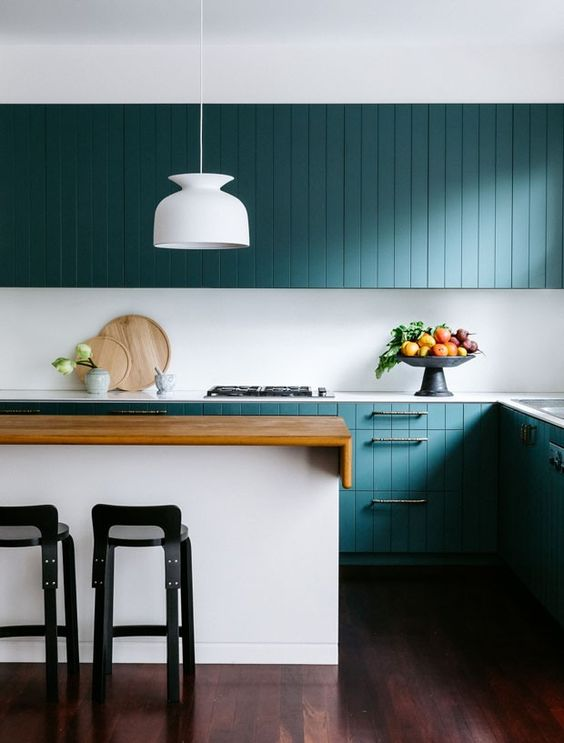a stunning turquoise coastal kitchen with beadboard cabinets, a white kitchen island with a stained countertop, black stools and a white pendant lamp