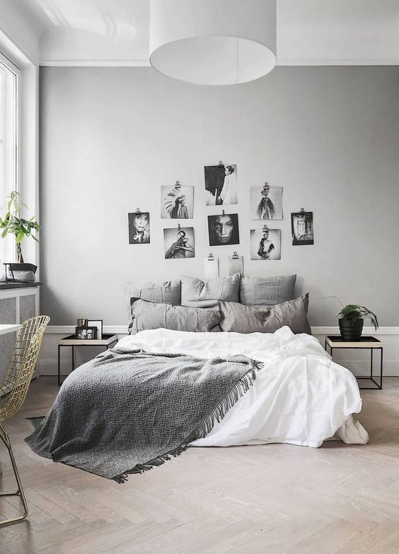 a stylish Nordic bedroom with dove grey walls, grey and white bedding, a gallery wall and touches of black