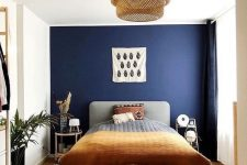 a stylish bedroom with a navy accent wall, a grey bed with printed bedding, woven lamp, mismatching nightstands and potted greenery
