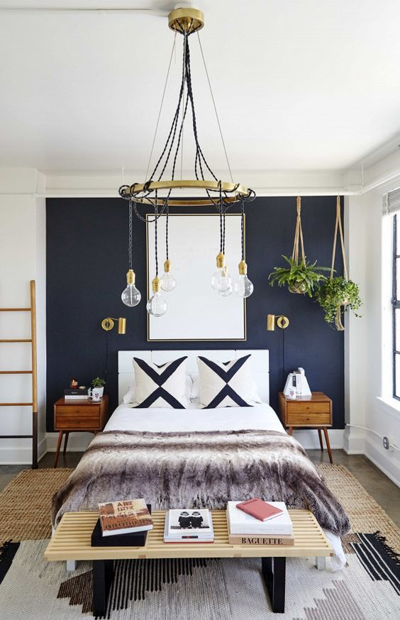 a stylish boho chic bedroom with a navy wall, stylish mid-century modern furniture, touches of gold and potted plants