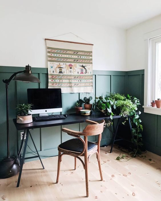 a stylish boho modern home office with hunter grene paneling, a black desk, a wooden chair and a folksy hanging on the wall