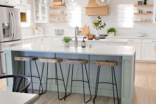 a stylish coastal farmhouse kitchen with white cabinets, a light blue island, wooden shelves and a hood, weathered wood stools