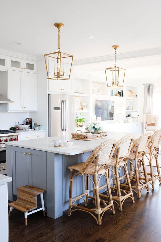 a stylish coastal kitchen with white cabinets, a blue kitchen island, rattan chairs, gold pendant lamps and gold knobs