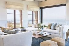 a stylish coastal living room with large windows including a panoramic one, with shades, leather ottomans and touches of blue