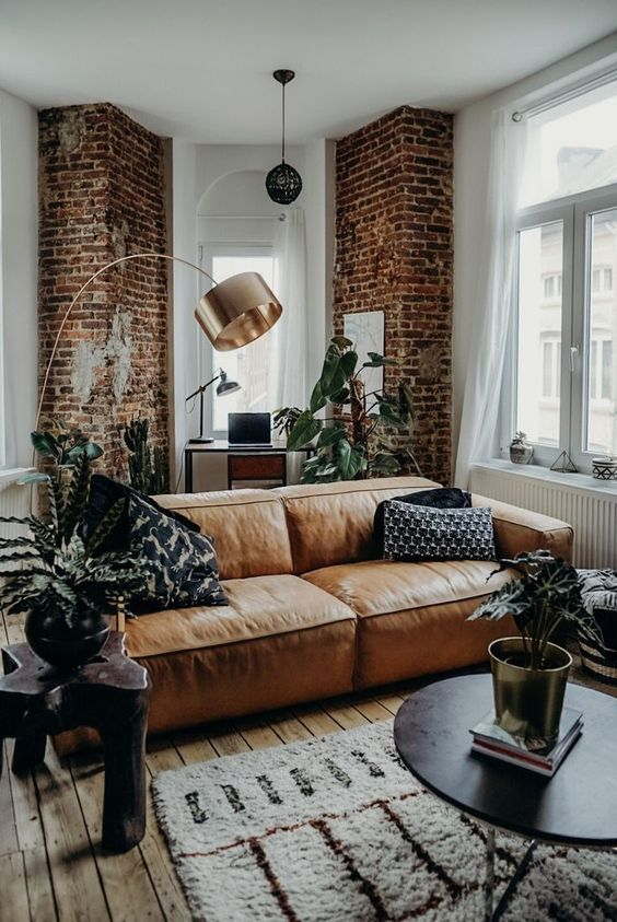 a stylish contemporary and industrial living room accented with red bricks and an amber leather couch