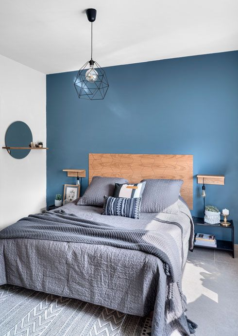 a stylish contemporary bedroom with a blue accent wall, navy nightstands, grey and navy printed bedding and a geometric lamp
