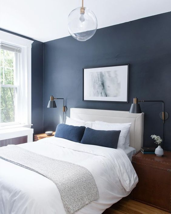 a stylish contemporary bedroom with navy walls, a white leather bed, wooden chests as nightstands and navy pillows