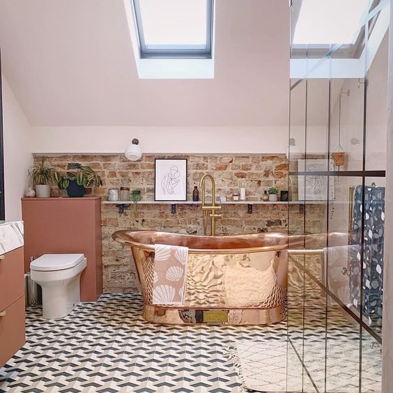 a stylish eclectic bathroom with a mosaic tile floor, a brick wall, skylights and a copper bathtub that is a centerpiece here