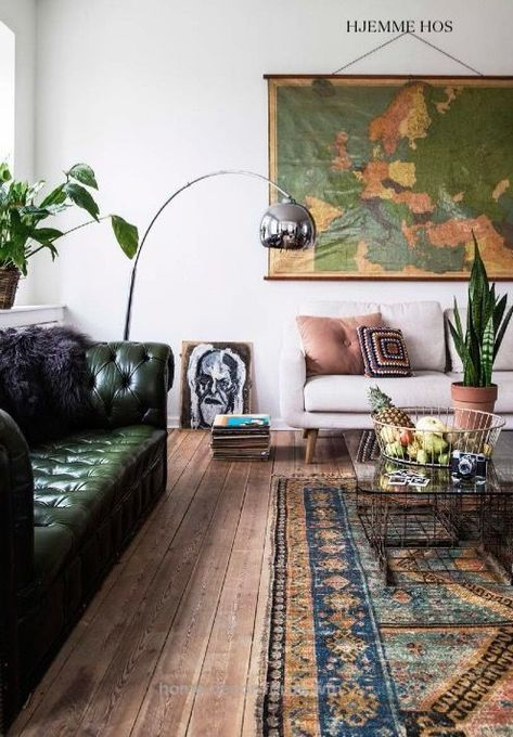a stylish eclectic living room with a green leather tufted sofa and a more neutral couch for a contrast