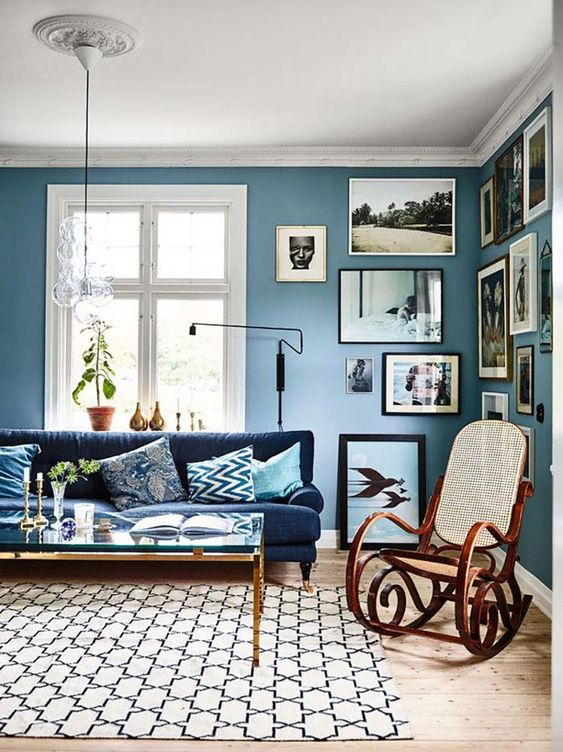 a stylish eclectic living room with blue walls, a navy sofa, a gallery wall and touches of gold for more chic