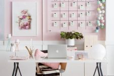 a stylish feminine home office with a light pink accent niche, a memo board, a trestle desk and a chair plus chic accessories