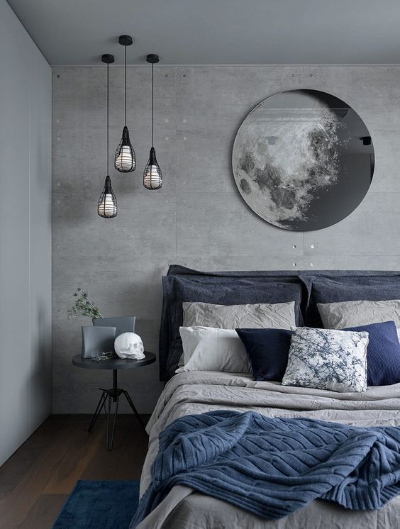 a stylish grey bedroom with concrete walls and a storage unit, a grey bed with grey and navy bedding, a grey side table and a gorgeous moon artwork