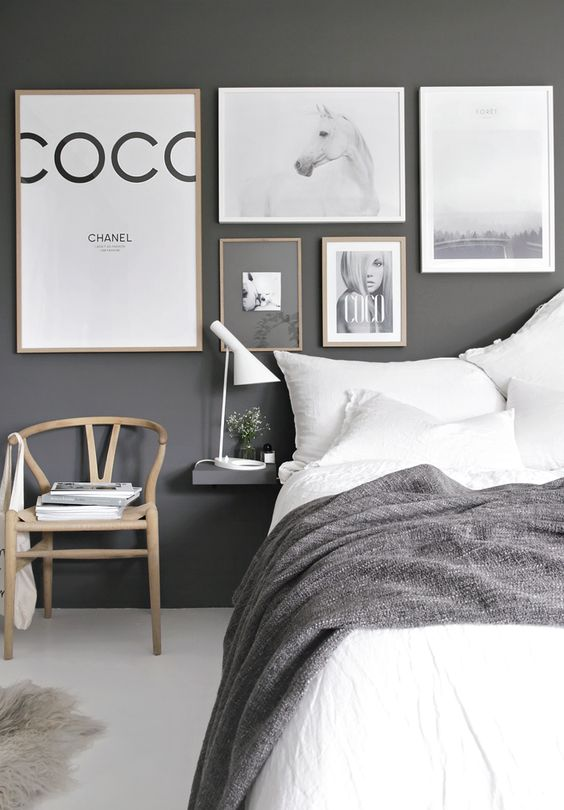 a stylish grey bedroom with graphite grey walls, a gorgeous gallery wall, white and grey bedding and touches of light colored wood