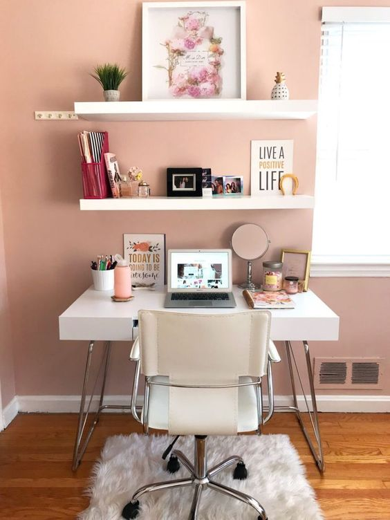 a stylish home office nook with a dusty pink wall, white furniture, open shelving and nothing unnecessary