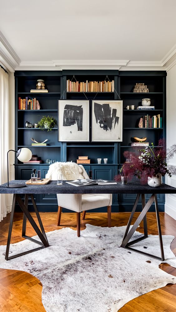 a stylish home office with a blue storage unit that takes a whole wall, a catchy desk with a stone countertop and a creamy white chair
