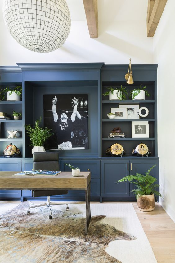 a stylish home office with a blue storage unit that takes one wall, a wooden desk, a leather chair and touches of greenery and gold