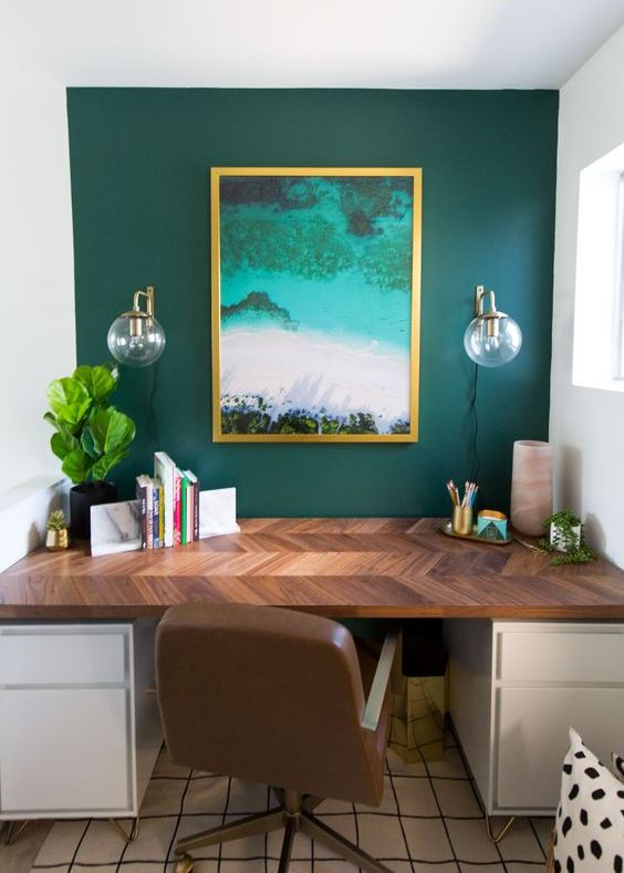 a stylish home office with a hunter green accent wall, a bright artwork, a stylish desk with a patterned tabletop