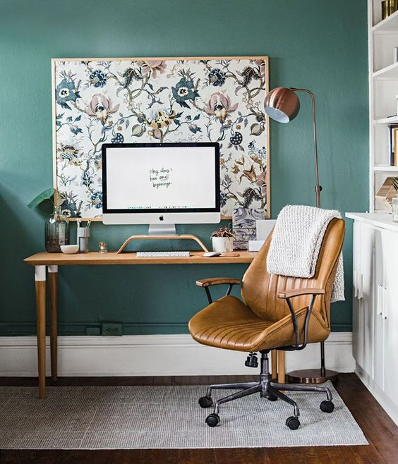 a stylish home office with sage green walls, wood and leather furniture, a large artwork is very welcoming
