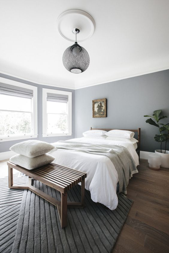 a stylish minimal bedroom with grey walls, a refined grey pendant lamp and a striped rug is welcoming