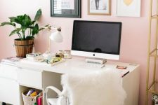 a stylish modern home office with light pink walls, neutral furniture, a glam gallery wall, gold touches for a chic feel