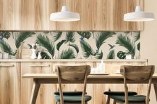 a stylish modern kitchen with sleek wooden cabinets, a tropical leaf backsplash and green chairs that echo with it