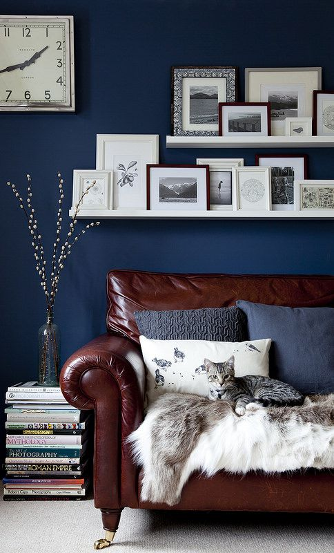 a stylish navy living room with a chocolate brown leather sofa and a chic gallery wall on ledges