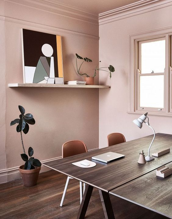 a stylish sahred home office in pale pink, with two trestle desks, open shelving, potted plants and an abstract artwork