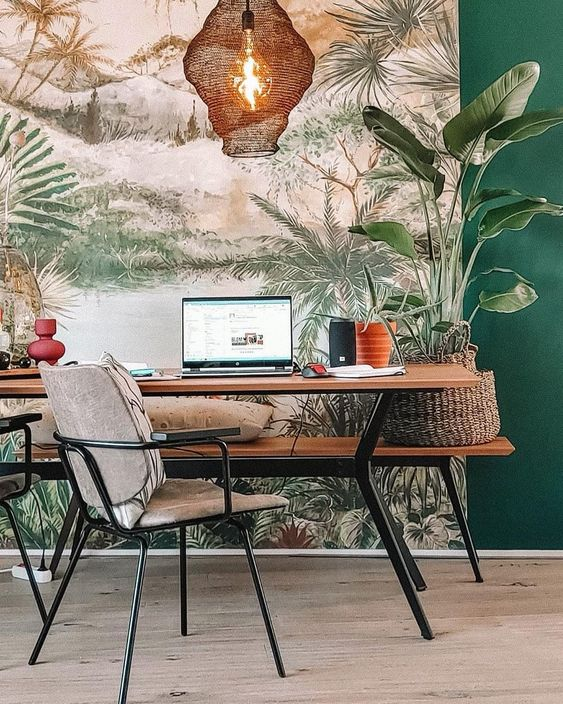 a stylish tropical home office with a tropical wall mural, a wooden desk and a bench, potted plants and woven elements