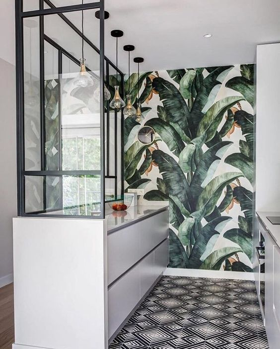 a stylish tropical kitchen with a banana leaf wall, white sleek cabinets, a mosaic floor and pendant lamps