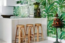 a stylish tropical kitchen with a tropical leaf wall, sleek white cabinets, rattan stools and a jute rugs reminds of beaches