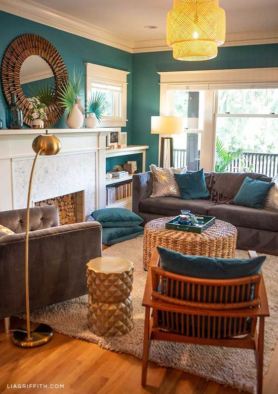 a stylish tropical living room with emerald walls, grey furniture, teal pillows, rattan elements and tropical leaves