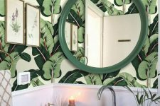 a stylish tropical powder room with banana leaf wallpaper, a grene framed mirror, a white bowl sink and some greenery