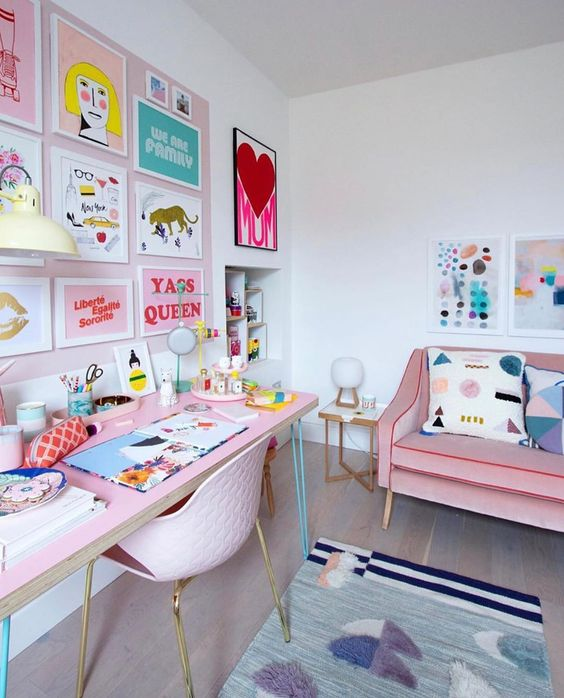a super bright and fun feminine home office with a pink accent wall with a crazy gallery wall, a pink desk and a sofa, a bright rug and pillows