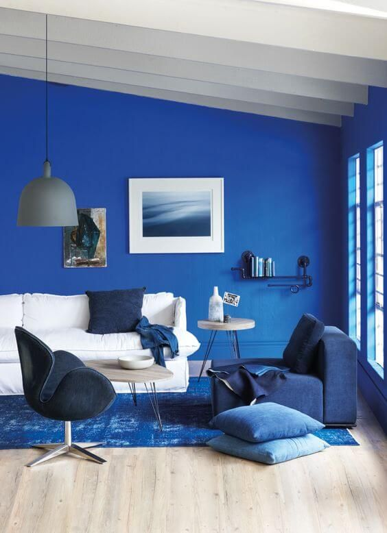 a super bright monochromatic classic blue and navy living room with a sea gallery wall and refreshing touches of white