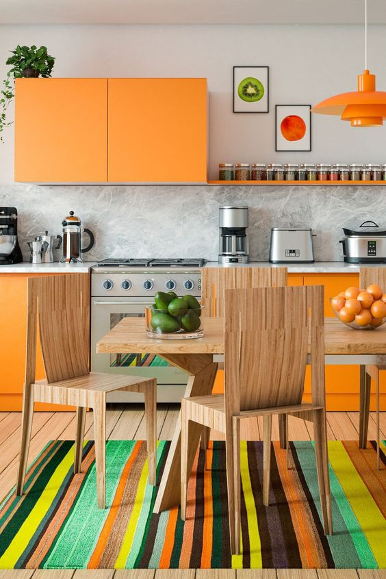 a super colorful kitchen with sleek orange cabinets, a marble backsplash and countertops, stained dining furniture and a colorful rug