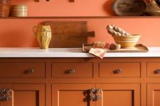 a terra cotta kitchen with burnt orange walls and white stone countertops is a stylish and chic space