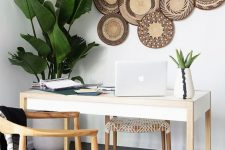 a tropical-inspired home office with decorative baskets on the wall, potted plants, woven chairs looks unusual and relaxed