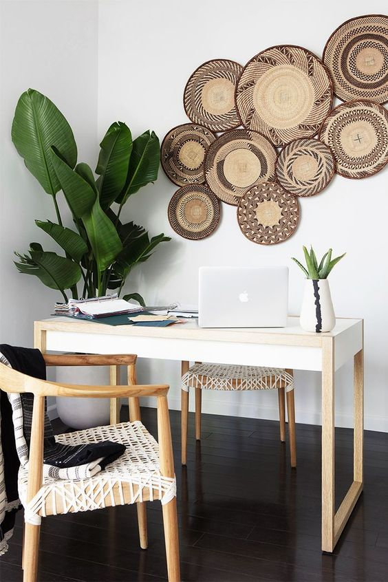 a tropical inspired home office with decorative baskets on the wall, potted plants, woven chairs looks unusual and relaxed