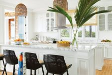 a tropical kitchen in white, with white cabinets and stone countertops, rattan pendant lamps and black stools