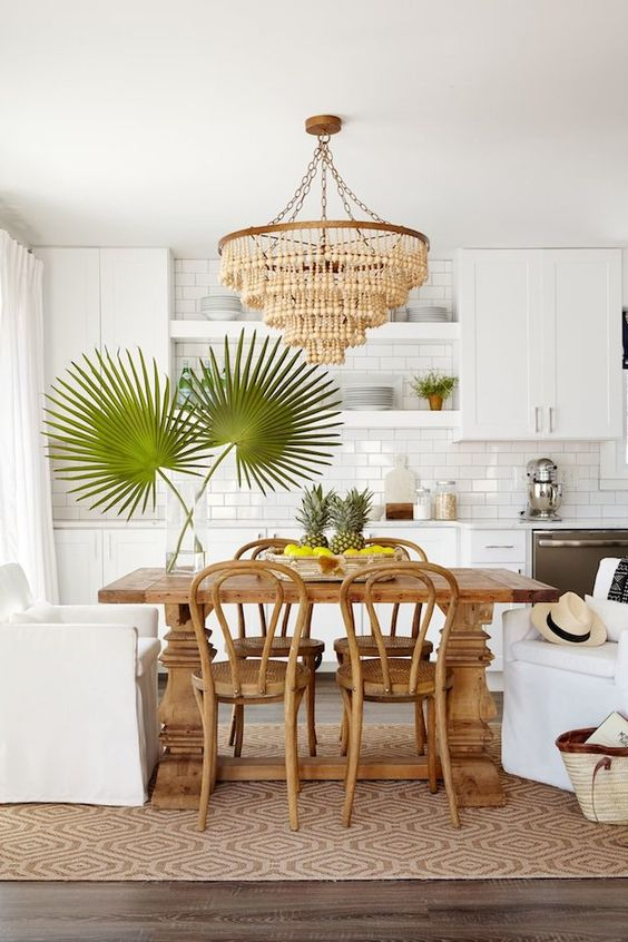 a tropical kitchen with white cabinets, a subway tile backsplash, a wooden table and chairs plus a bead chandelier and tropical leaves