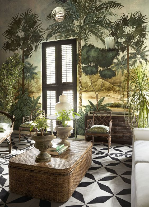 a tropical living room with catchy wallpaper, vintage-inspired rattan furniture, potted greenery and a mosaic tile floor