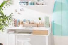 a tropical pastel home office with a shabby green rug, a color block surfing board and potted greenery